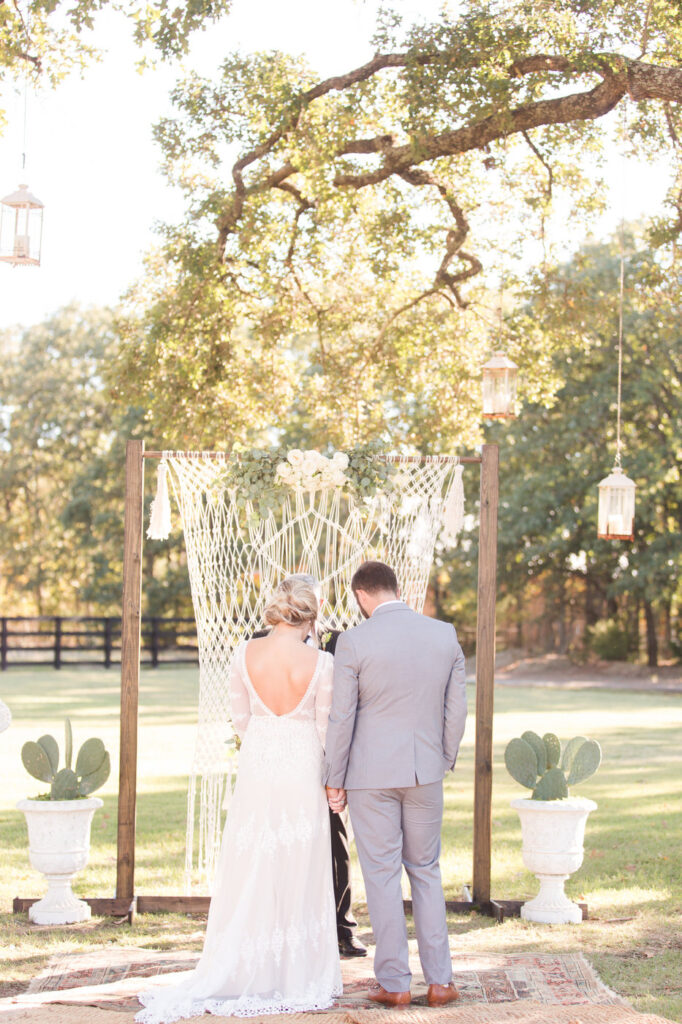 bride and groom standing with their backs to the audience in front of a macrame backdrop during the ceremony