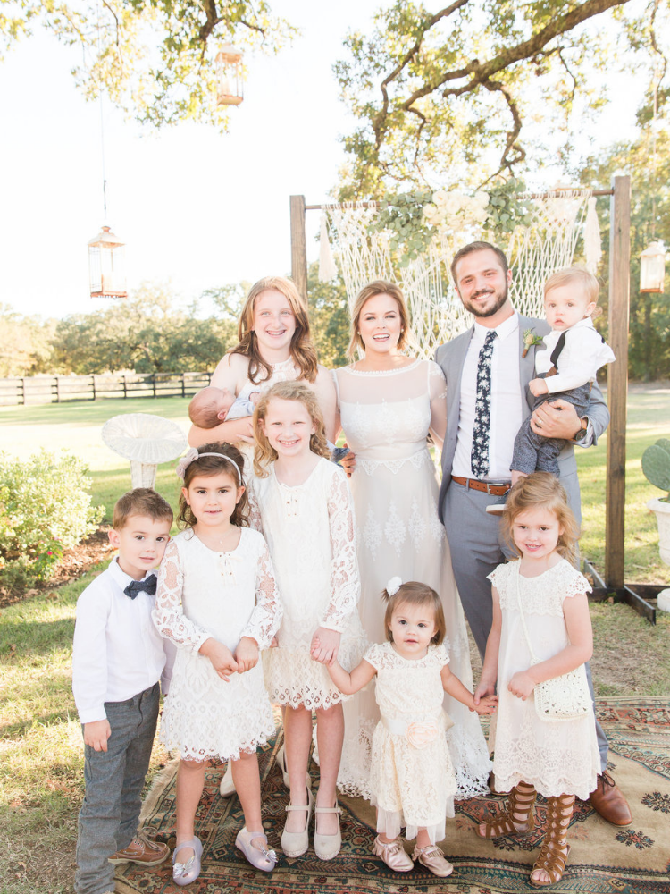bride and groom standing in front of macrame wedding backdrop with children that were a part of the wedding