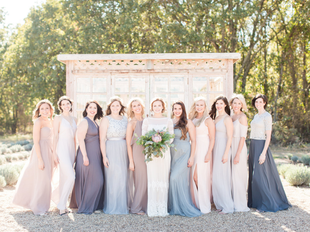 10 bridesmaids and the bride all dressed in neutral color dresses standing in front of a greenhouse in a lavender field