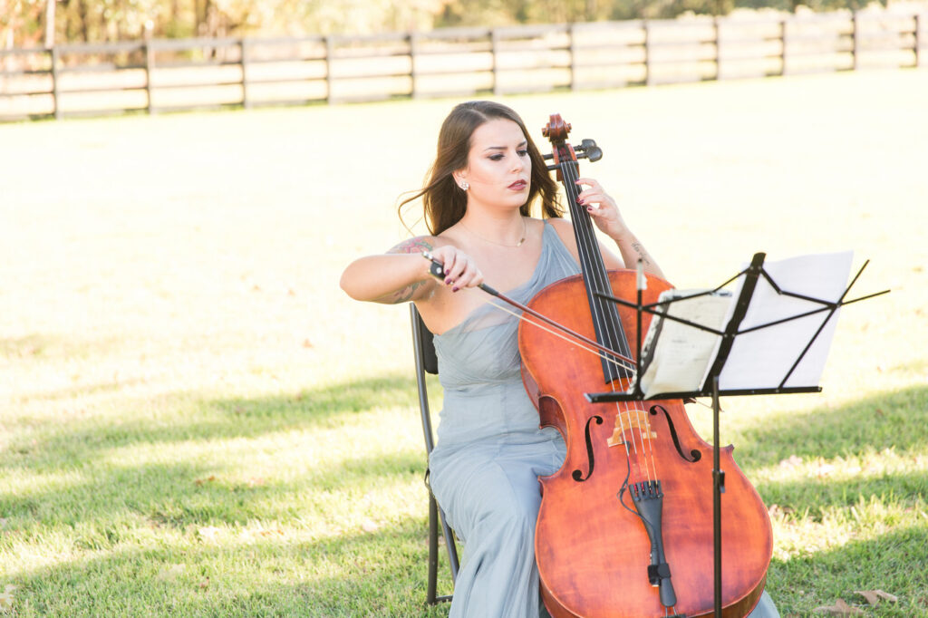 Cellist playing outside at a boho style wedding ceremony