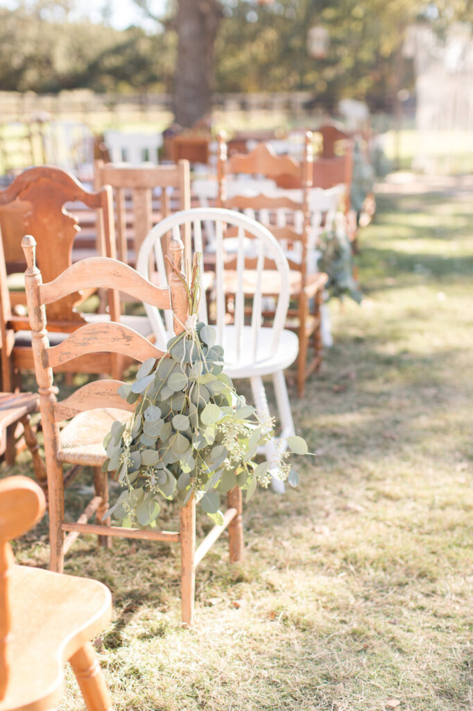 mix matched vintage chairs set up outside the wedding venue for a boho style wedding ceremony