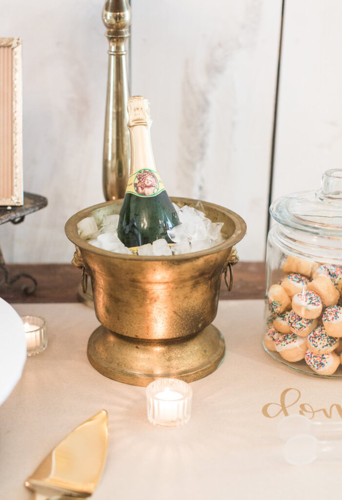 champagne in vintage brass wine bucket for bride and groom toast