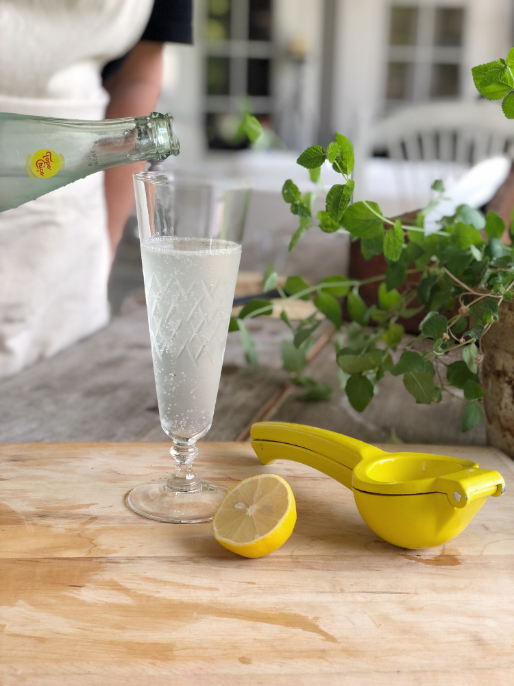 pouring topo chico over other liquids in citrus rosemary cocktail