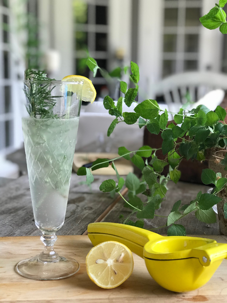 champagne flute with citrus rosemary cocktail. Lemon wedge on the side of glass for garnish and a sprig of rosemary inside the glass
