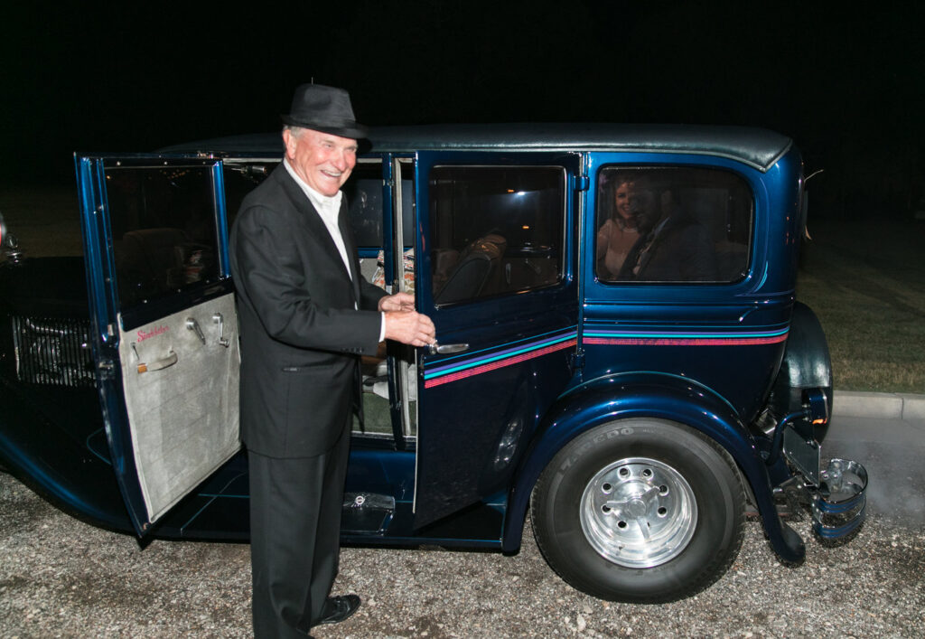 brides grandfather standing by a vintage Studebaker to take the bride and groom away