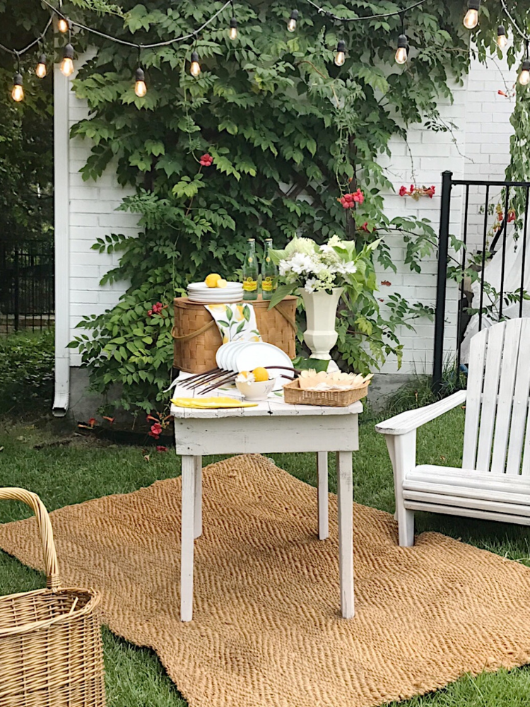 outdoor picnic tablescape in front of a wall of trumpet vine.  white picnic table has white plates, lemon print napkins, white flowers in a white vintage vase, a vintage picnic basket and bamboo utensils and 4 bottles of Topo Chico