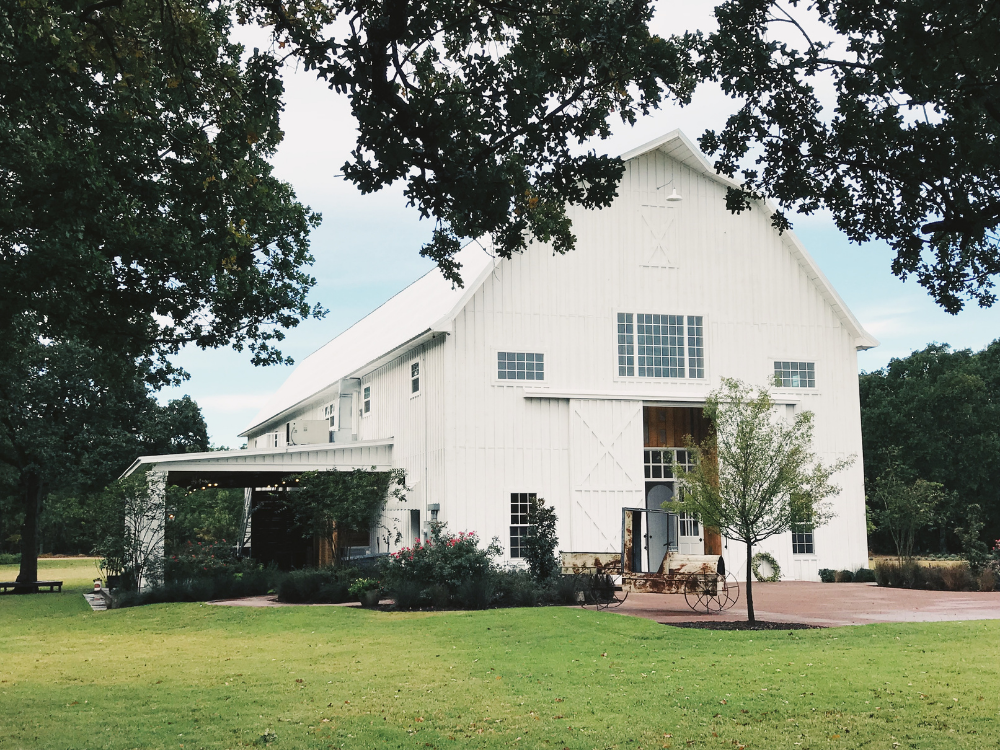 the exterior of a beautiful white barn wedding venue