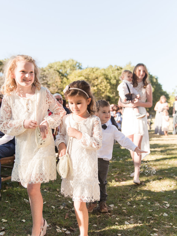 flower girls walking down the aisle at an outdoor wedding