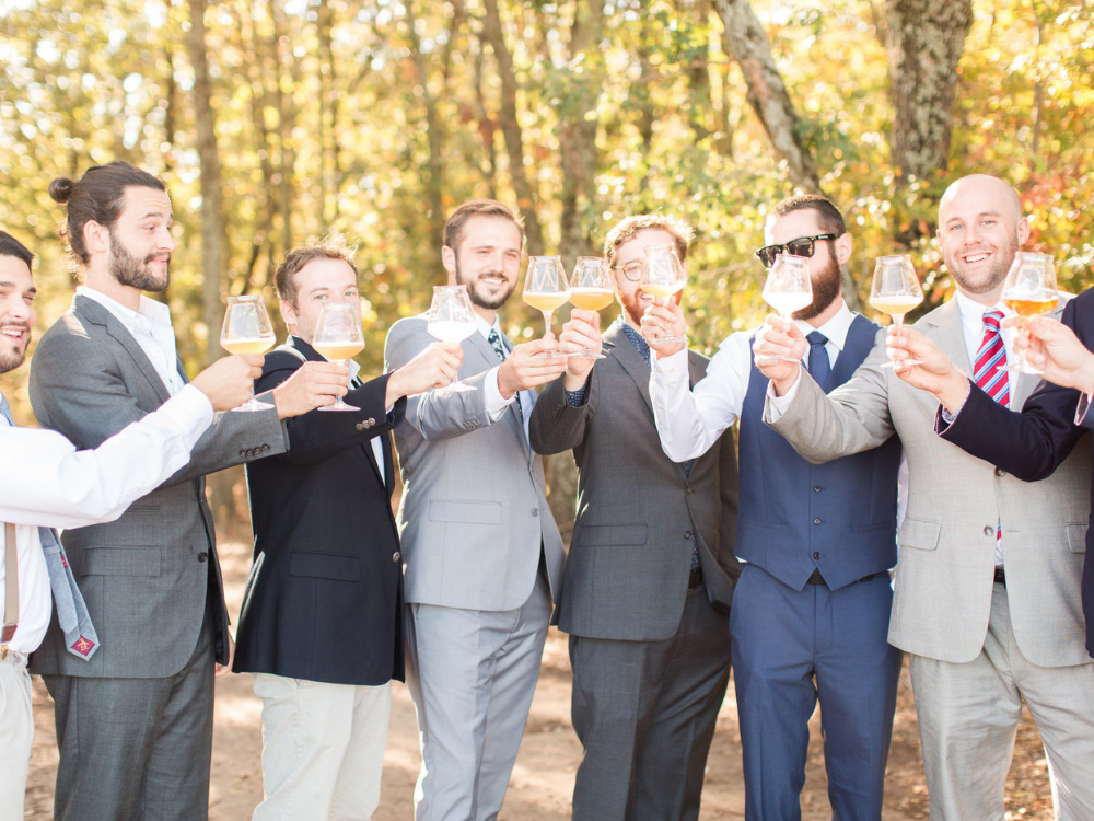 Groomsmen outdoors toasting the groom with a beer