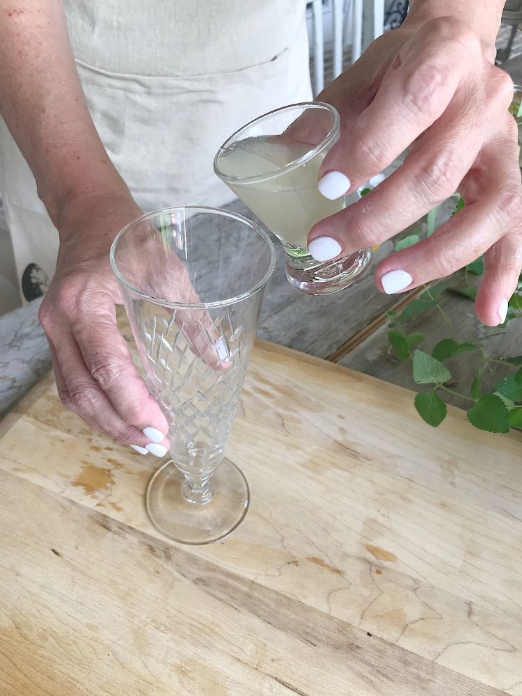 Pouring lemon juice into a champagne glass