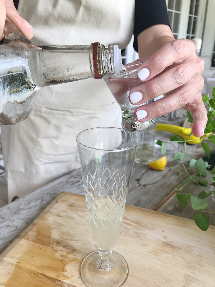 pouring vodka into a clear glass champagne glass