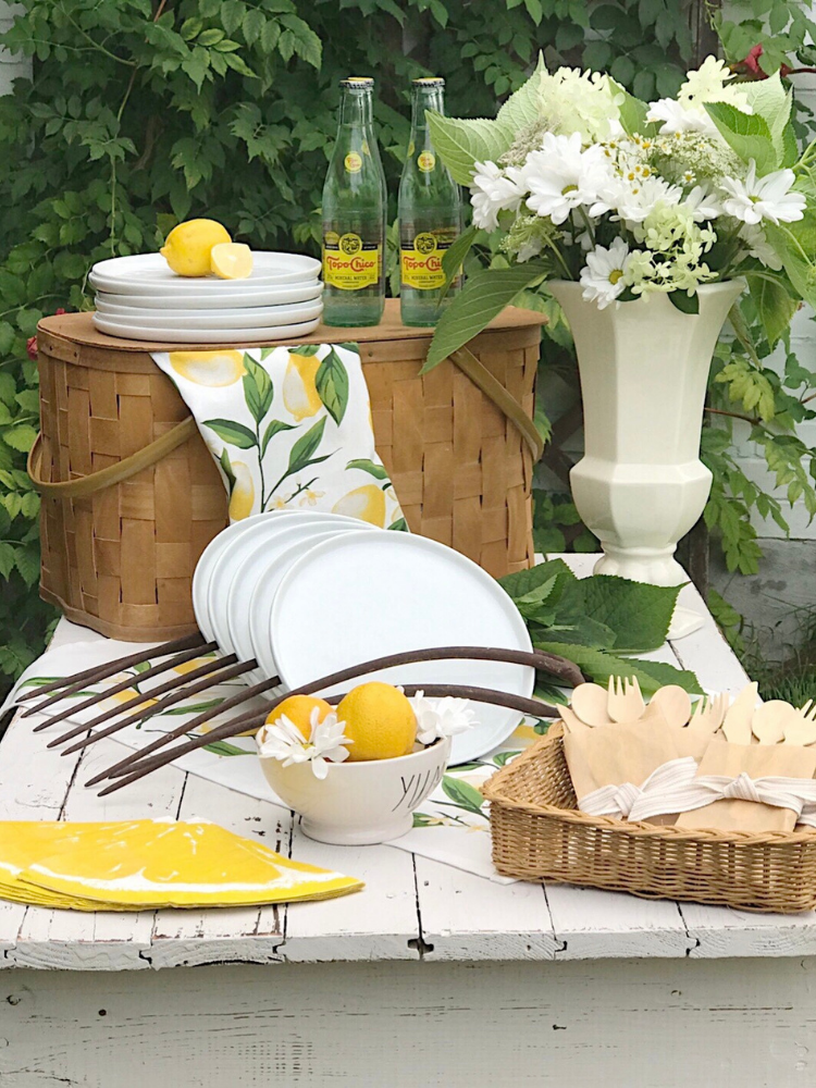 Outdoor picnic tablescape with white plates on a white table, white flowers in a vintage white vase, lemon print napkins, bamboo utensils and a vintage picnic basket