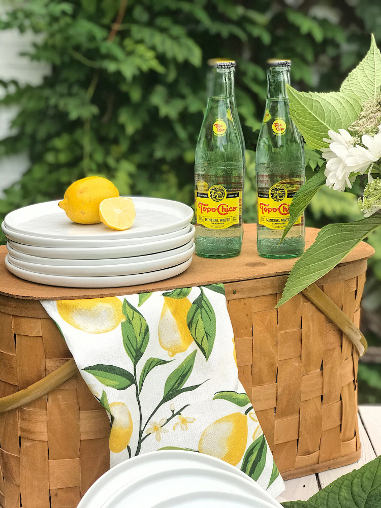 vintage picnic basket, with a stack of white plates on top and 4 bottles of Topo Chico.  A lemon print dishtowel is draped over the picnic basket