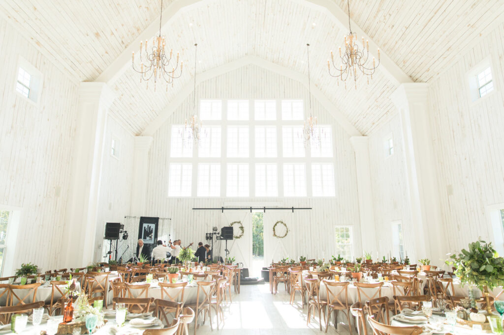 the white barn wedding venue inside with tables set for reception