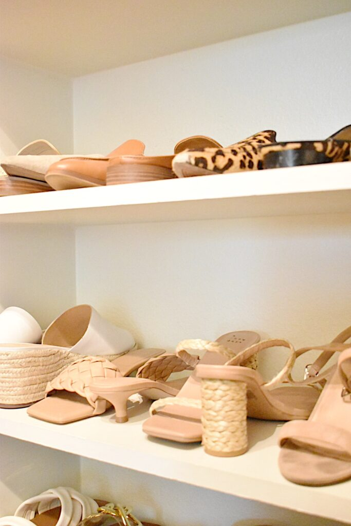 shoes stacked neatly on shoe shelves in closet