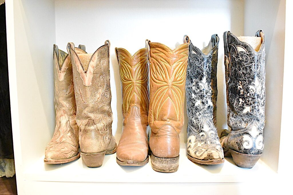 3 pair of cowboy boots on closet shelf with pool noodles inside to keep them standing straight