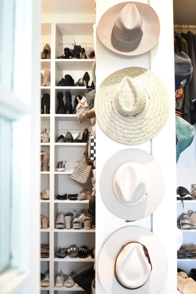 hats hanging on wall hooks inside closet for storage solution