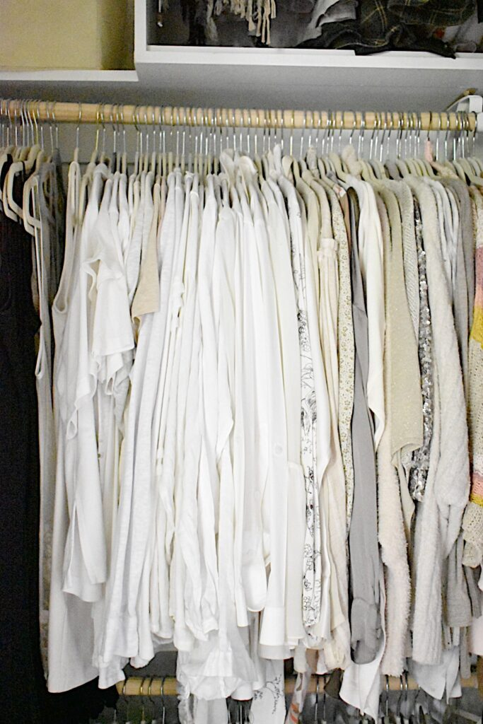 clothes hanging in color coded order inside clothes closet