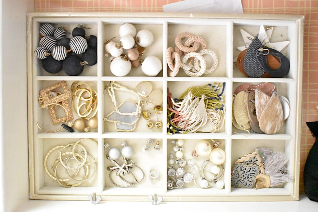 divided jewelry divider placed inside the drawer of the small chest inside a closet holds earrings
