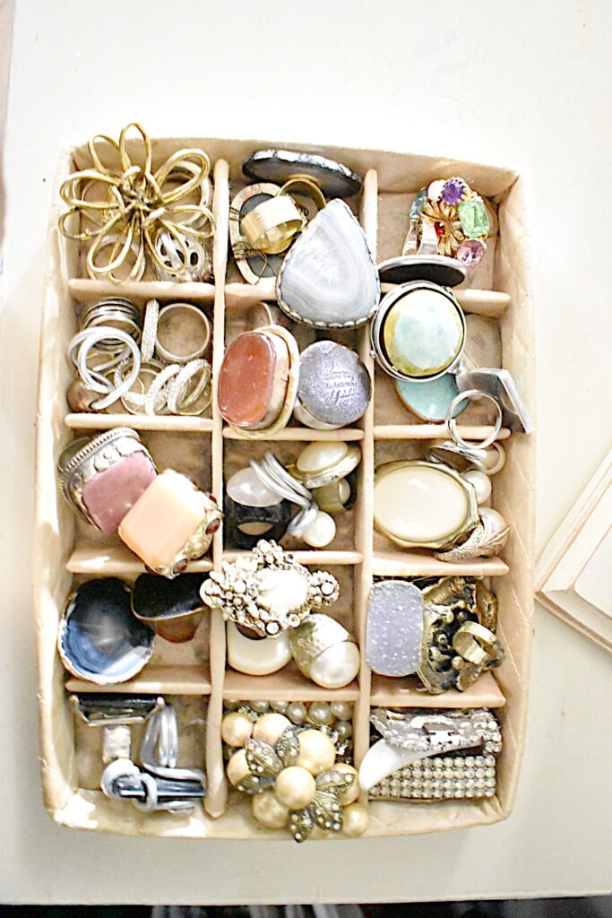 vintage divided jewelry organizer stands on a small dresser inside the closet to hold rings