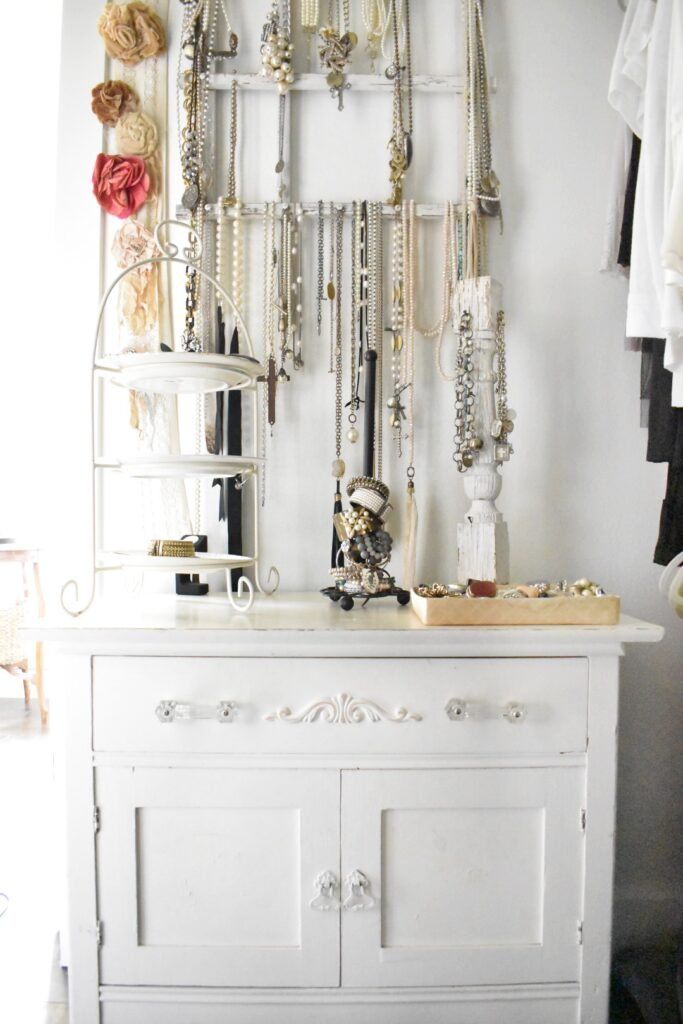 small white dresser with a white garden trellis mounted on the wall above.  The wall trellis holds necklaces and the dresser hold bracelets and other miscellaneous jewelry