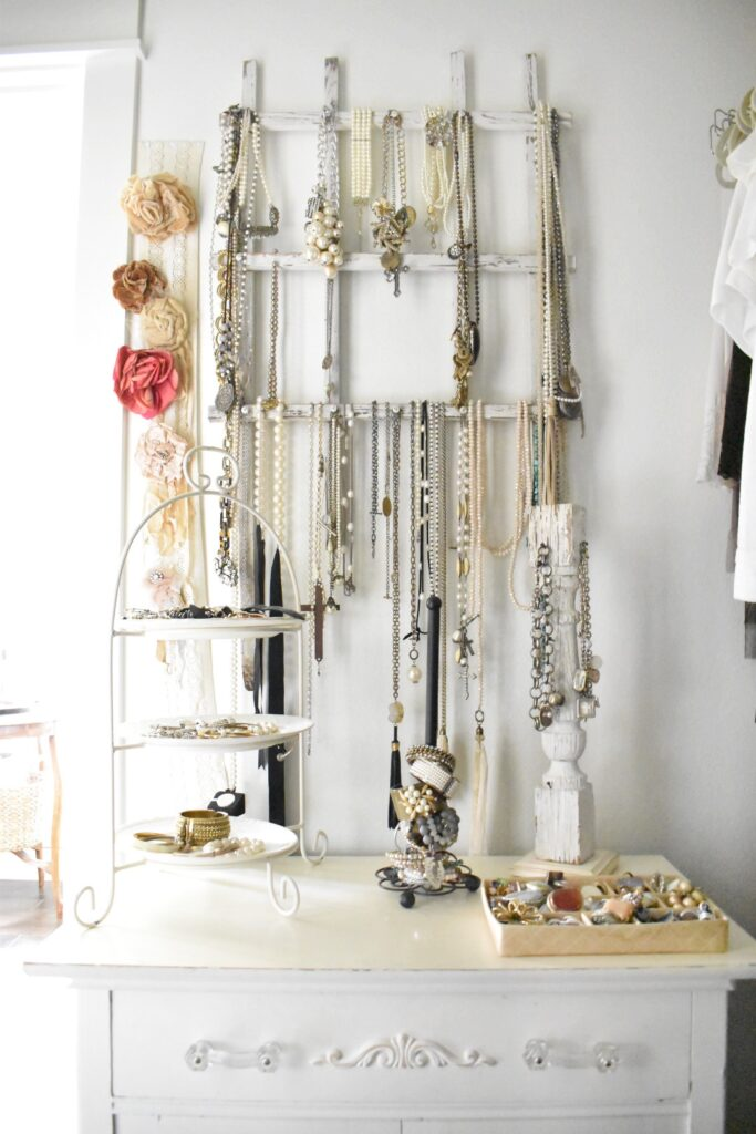 a white vintage garden trellis hanging on the wall inside a clothes closet to hang necklaces on