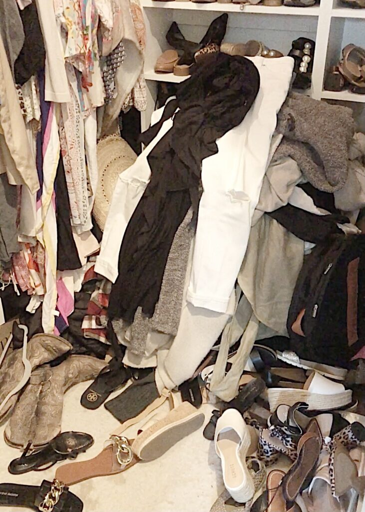 pile of clothes and shoes in messy clothescloset