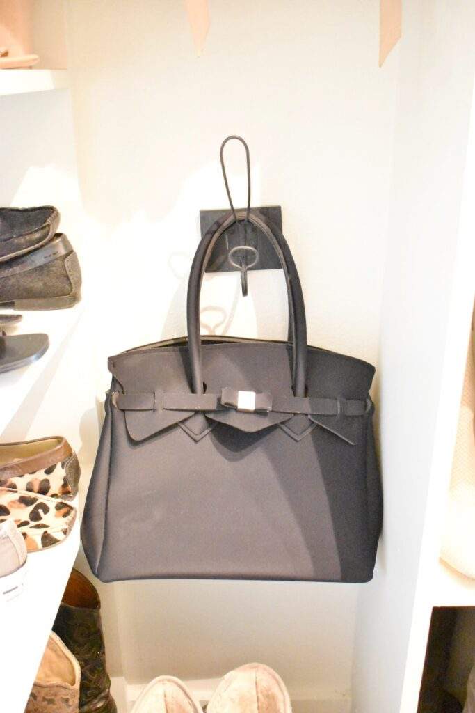 black handbag hanging on a wall hook for a storage solution in closet