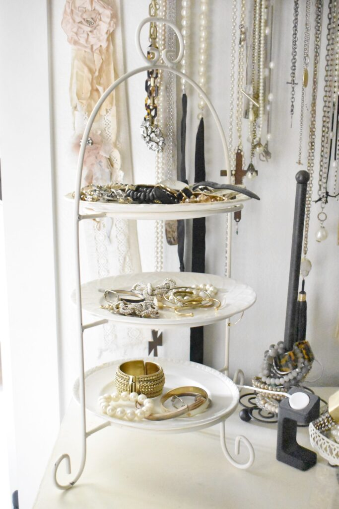 3 tiered plate stand with white plates hold bracelets and watches
