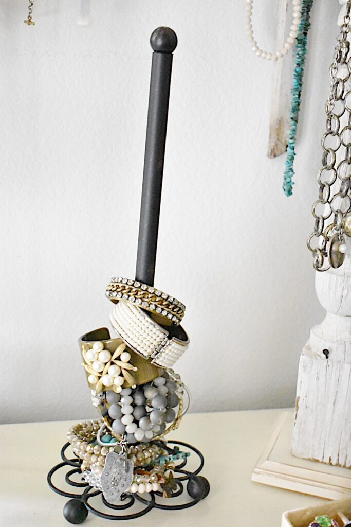 a black iron paper towel holder stands on a small dresser inside the closet for hold bracelets
