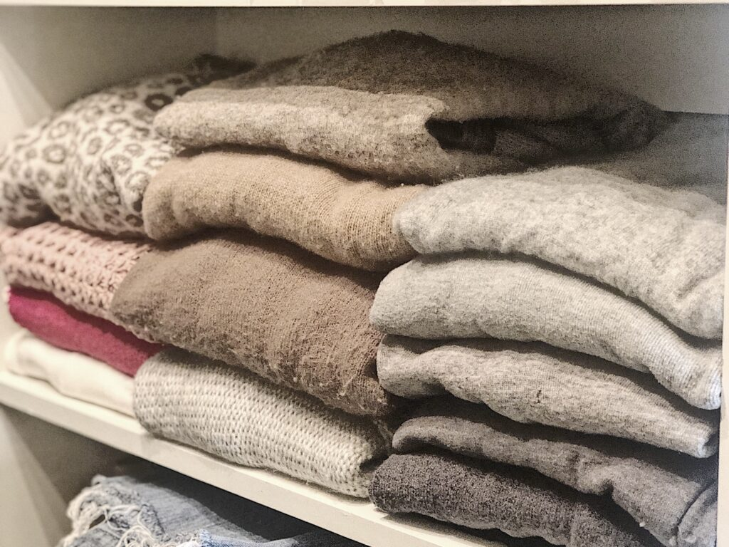 neutral sweaters folded and stacked on a closet shelf