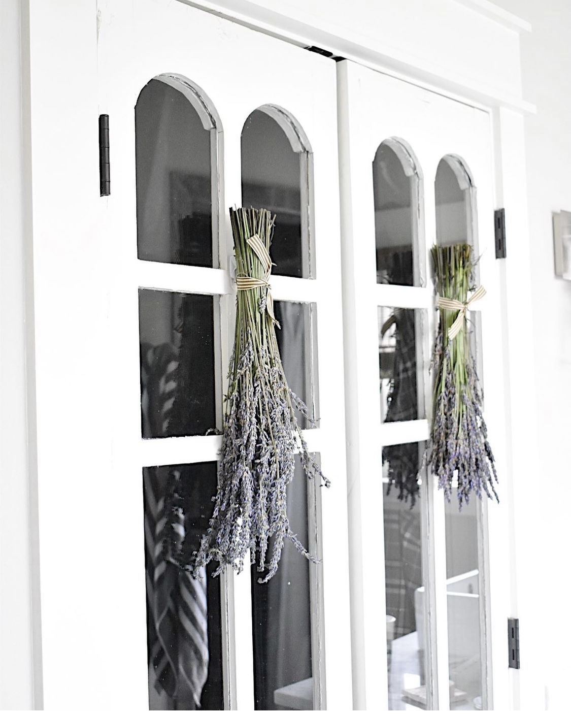 vintage closet doors with windo panes and bundles of lavender hanging on door for decoration