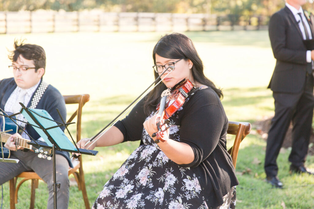violinist and guitarist at an outdoor wedding ceremony