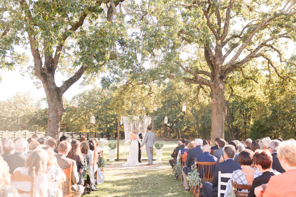 guests seated at an outdoor wedding in mismatched vintage chairs