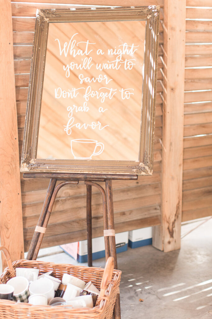 a quote written on a large vintage mirror standing on an easel, giving directions about taking a coffee mug for a party favor