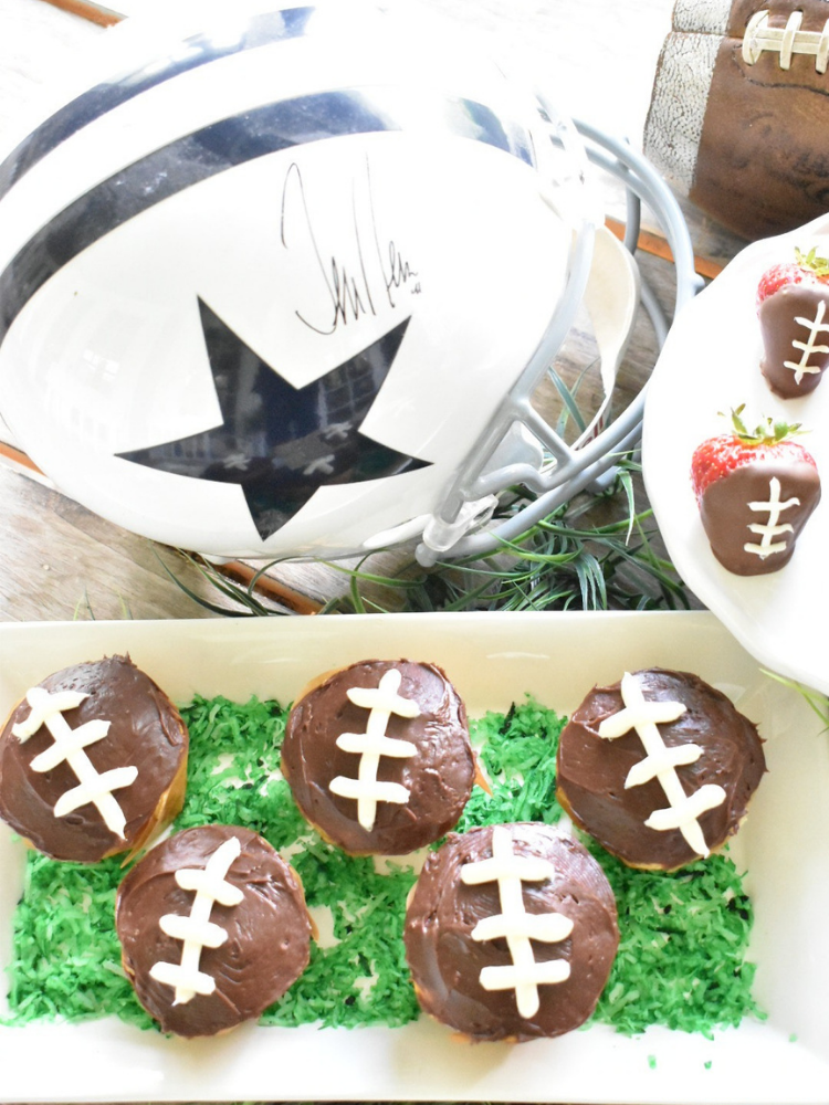 cupcakes with chocolate frosting and threads piped on with white frosting to resemble footballs
