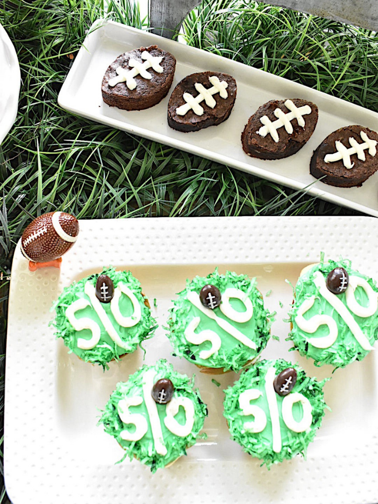 cupcakes with green frosting and a white stripe piped with vanilla frosting down the center and a 50 to resemble a football field 50 yard line