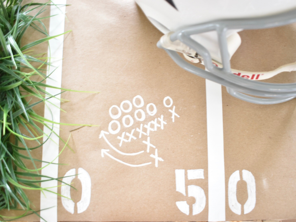 football plays written on the brown paper table runner with a white paint pen for added decoration