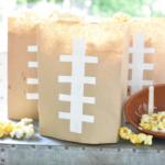 brown lunch sacks with white electrical tape cut and stuck on front to resemble the threads on a football, bags are filled with popcorn
