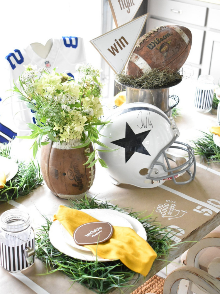 football tailgate party tablescape with football helmet football made into vase with flowers, faux grass placemats and yellow napkins to resemble penalty flags