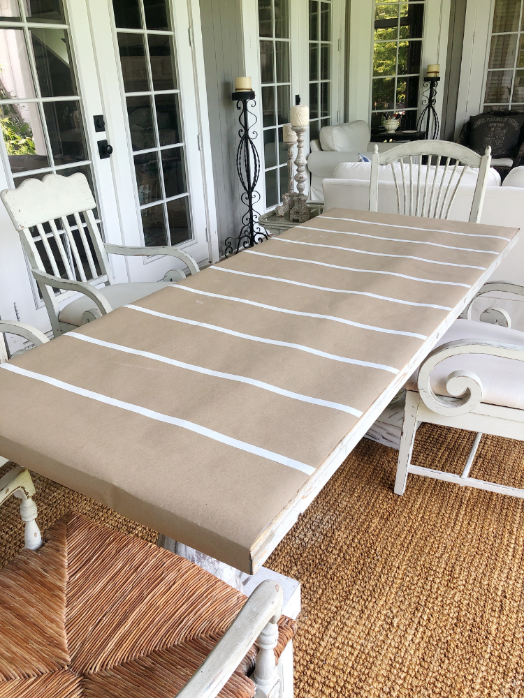 brown paper rolled out on dining table to create a table runner.  white electrical tape creates yard lines