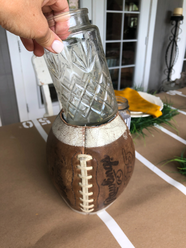 old football with both ends cut off to use as a vase.  Glass vase being placed inside football to hold water and flowers