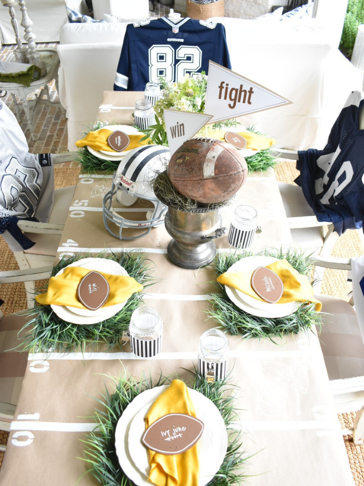 football tailgate themed tablescape with brown paper table runner and white tape to resemble yard lines, faux grass placemats, football jersey for chair covers