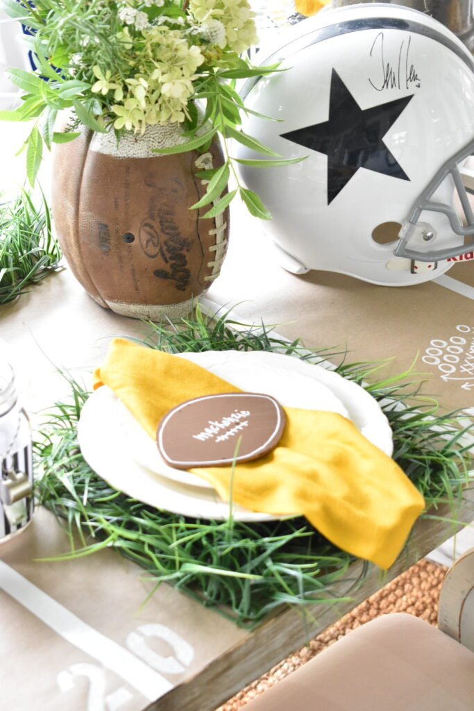 football theme place setting. faux grass square for placemat, white dinner plate stacked with white salad plate, yellow napkin and wooden football cutout on top of napkin for a place card