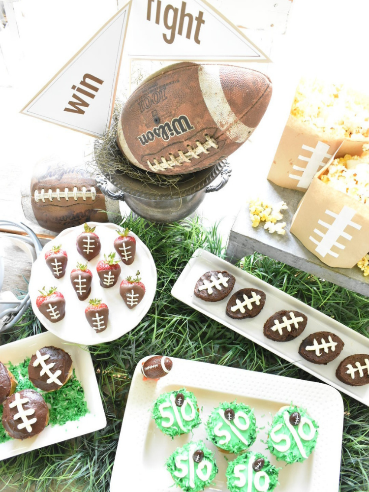 aerial view of football tailgate party dessert bar, brownie cut out of football shape cookie cutter and threads piped with white frosting, chocolate dipped strawberries with threads piped with frosting to look like footballs, cupcakes with green frosting piped with a center stripe and 50 piped on the top to resemble 50 yard line on a football field