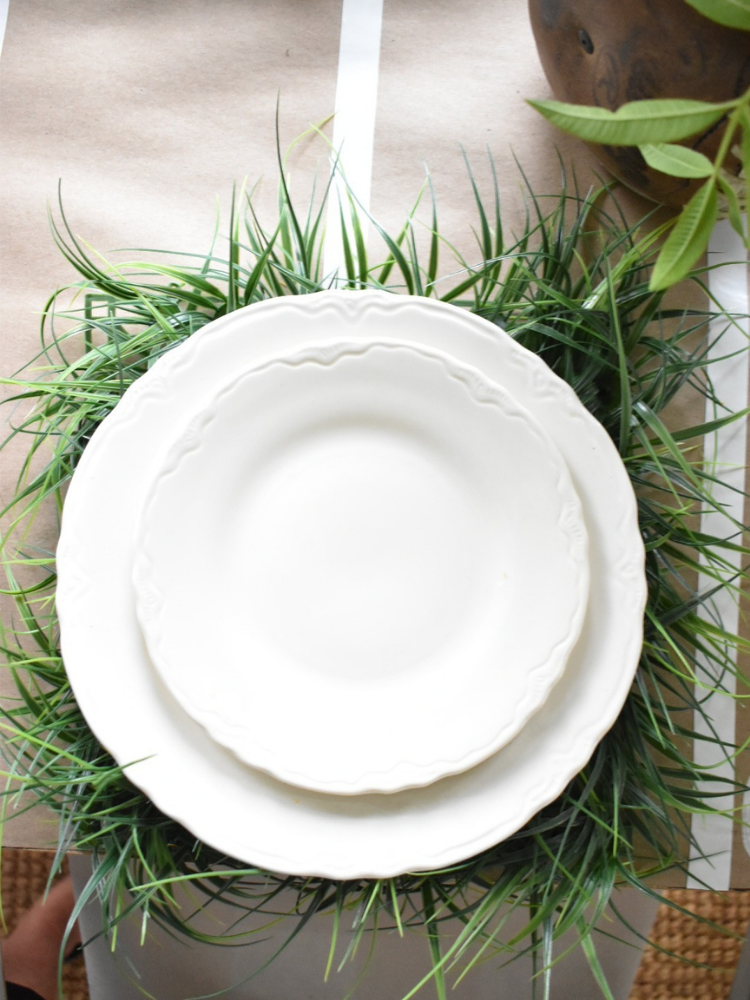 white dinner plate stacked with white salad plate on top of faux green grass square placemat