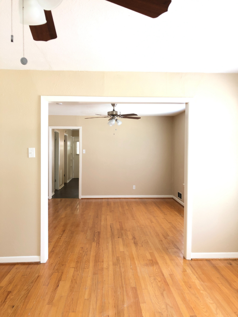 unfurnished dining room of a small cottage with tan walls and light hardwood floors