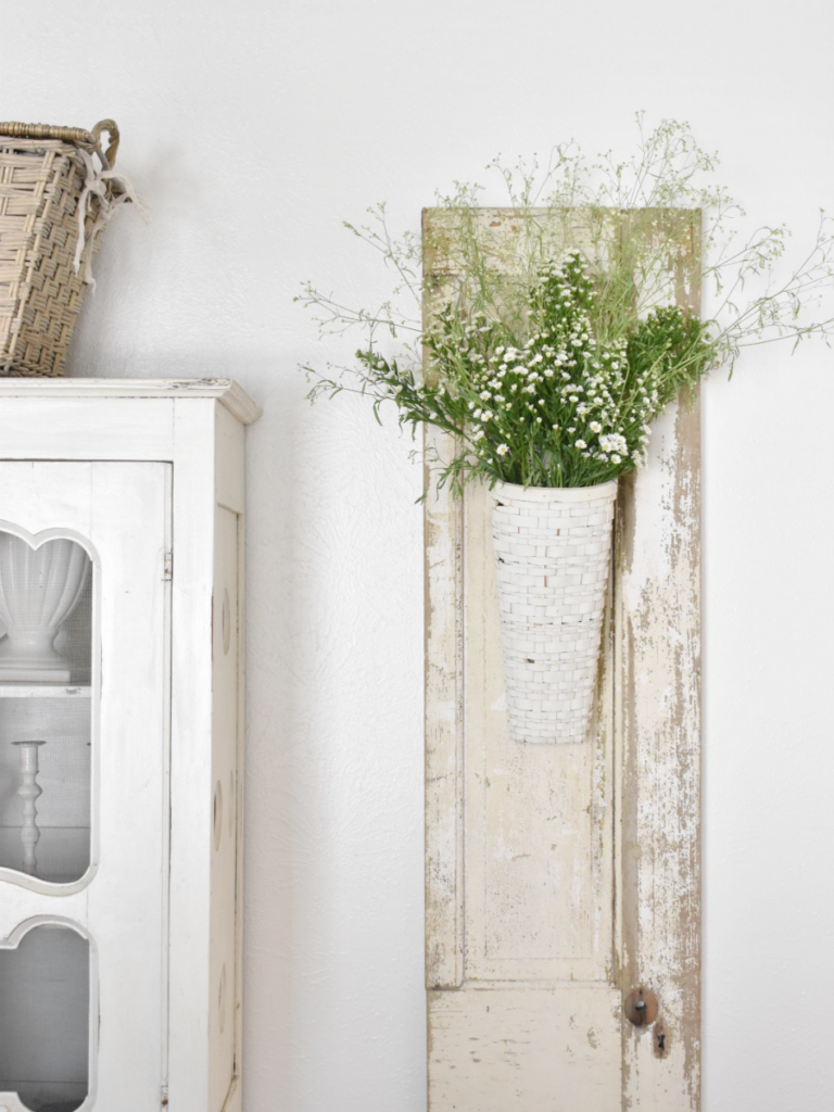 white chippy shutter hanging on wall with a white wall basket filled with wildflowers hanging on top of shutter