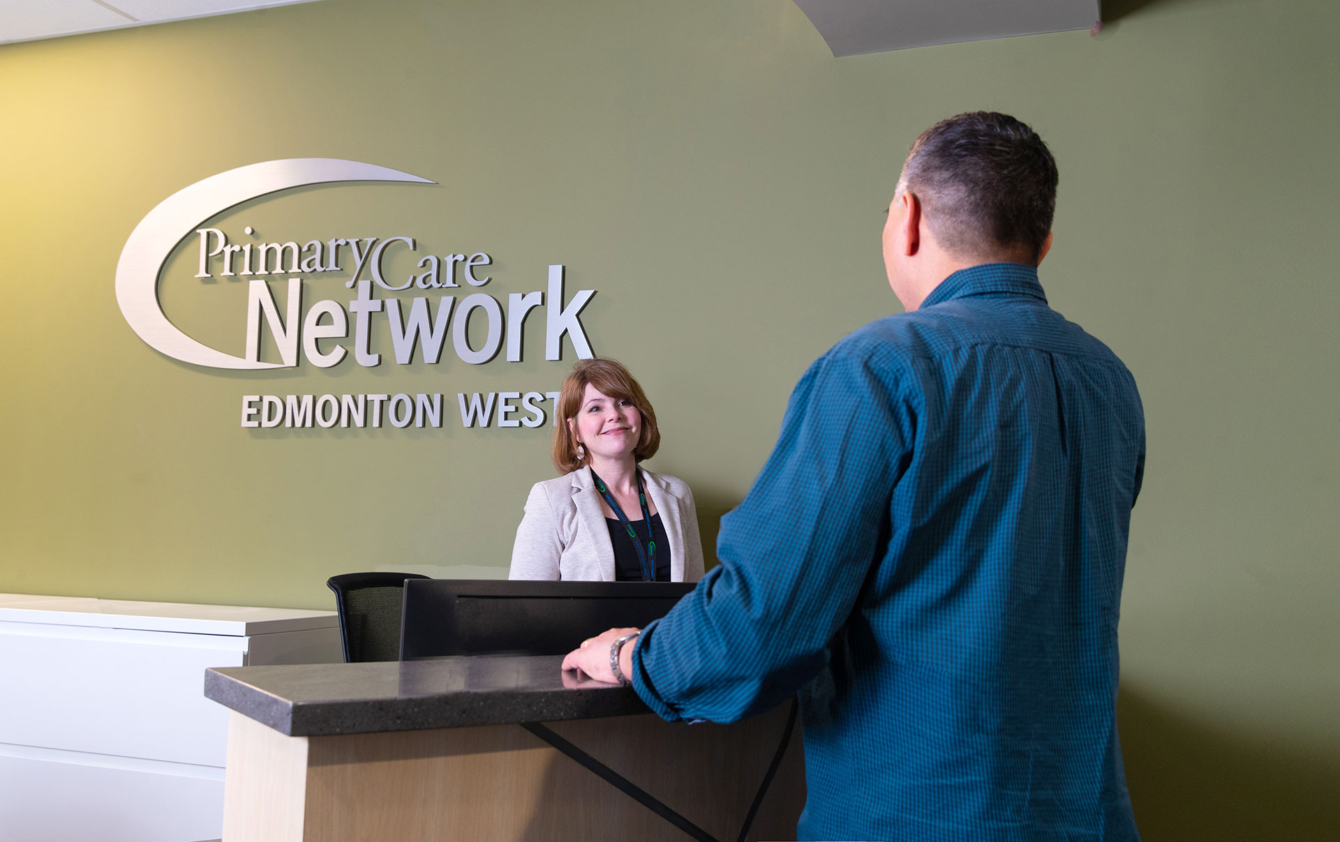 Two people standing at the Edmonton West Primary Care Network front reception area talking.