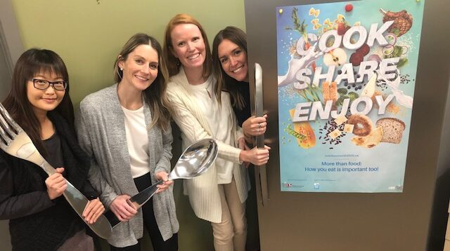 """Four dietitian staff members posing in front of a refrigerator holding fork and spoon props. Poster on fridge reads """"cook share enjoy"""""""